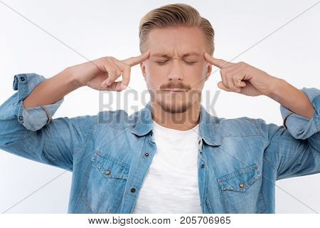 Unbearable migraine. Tired young man keeping his eyes closed and pressing his fingers to the temples while suffering from a splitting headache