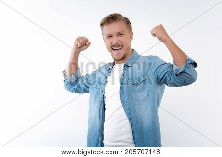 Achieving success. Beautiful young man clenching his fists and raising hands in a celebratory gesture, being happy about his achievements