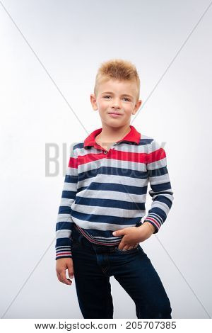 Cute preteen. Beautiful fair-haired little boy in a striped long sleeve t-shirt and jeans posing on a white background and holding his hand in a pocket