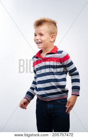 Cheerful kid. Handsome little boy with fair hair and blue eyes wearing a striped long sleeve t-shirt and jeans posing on white background and looking away
