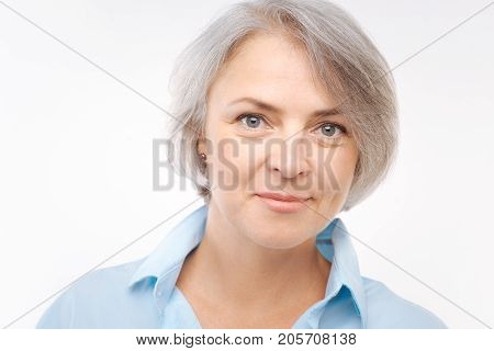 Charming lady. The portrait of a beautiful middle-aged woman with grey hair and grey eyes posing on a white background and smiling at the camera