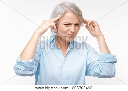 Stop being annoying. Irritated middle-aged woman pressing her fingers to the temples and looking angrily at someone annoying