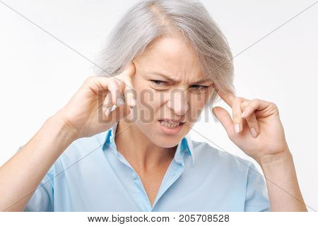 Throbbing pain. Irritated young woman pressing her fingers to the temples and suffering from a splitting headache while wincing