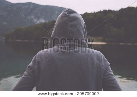 Gloomy nostalgic portrait of sad lonely melancholic adult female with hooded jacket standing on the lake shore in misty overcast morning and thinking in solitude about personal problems retro toned