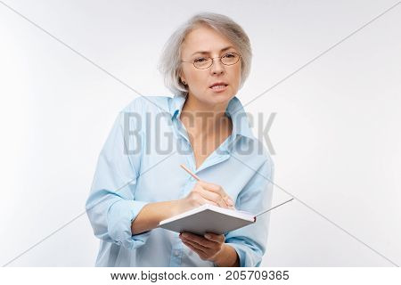 Paying attention. Concentrated grey-haired woman listening to someone speaking attentively and making notes of the speech in her notebook