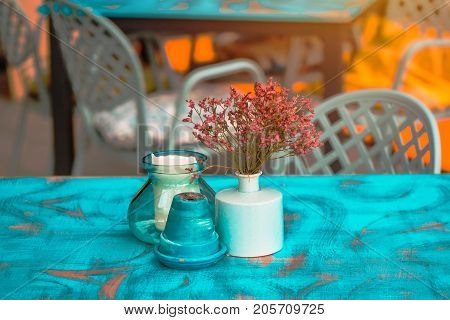 Modern hipster style teal and orange table arrangement in cafe or restaurant - flowers in pot ashtray and candle