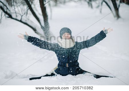 A girl in a black jacket and a black hat sits on a string in the snow and throws snow. Happy child after a snowfall. Snow on the trees.