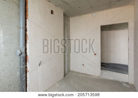 Small Kitchen In A New Building, Bare Concrete And Plastered Walls, Communications