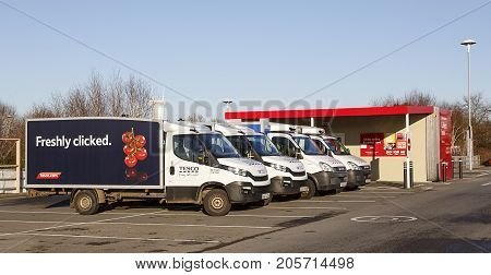 Swansea, UK: December 28, 2016: A row of Tesco delivery vans in front of a click and collect collection building. Shop online at Tesco direct and take advantage of next day Click & Collect.