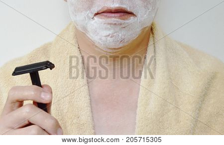 shaving cream on man face with black shaver on right hand prepare to shaved