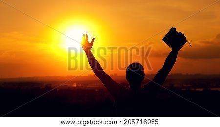 Silhouette of relaxed man enjoying sunset time, raising hands to the sky. Travelling and vacation concept.