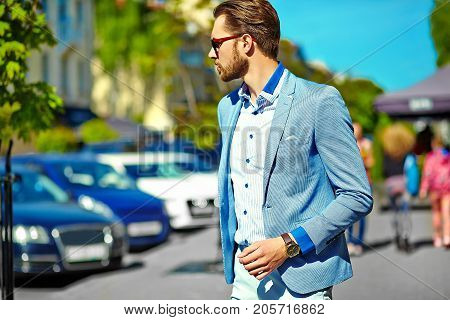 High fashion look.Young stylish confident happy handsome businessman model in suit clothes walking in the street