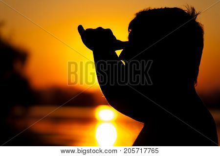 Silhouette of man looking into the distance at sunset time. Travelling and tourism concept. Relaxation and leisure.