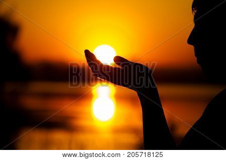 Silhouette of relaxed man enjoying sunset time holding sun in hands. Happiness and relaxation concept.