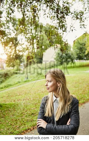 Blond and beautiful woman in park looking away