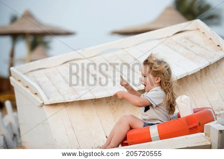 Travel and summer vacation. Marine safety and transport. Child little boy little sitting in life buoy on boat. Childhood and baby care concept. Small kid pointing with pointer finger at beach.