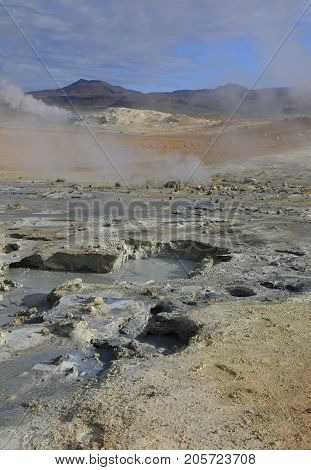 Fumaroles with volcanic boiling mud pots surrounded by sulfur hot springs in Hverir Namafjall geothermal place in Iceland