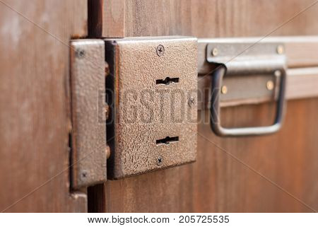 Brown door with two keyholes and a handle. Wooden door to the barn