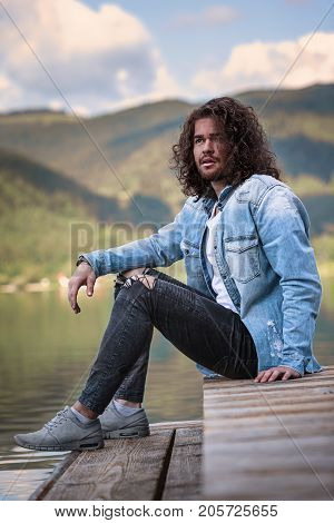 Portrait of a handsome young man with long hair sitting on a footbridge on the lake and enjoying the tranquility.