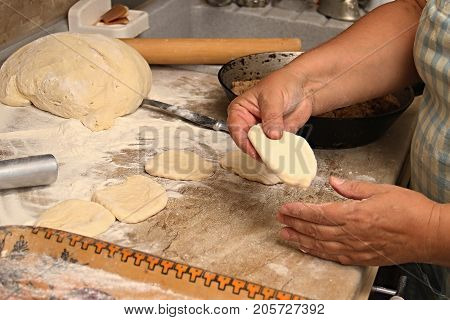 Senior woman baking pies in her home kitchen.Grandma cooks pies. Home cooked food. omemade mold cakes of the dough in the women's hands. The process of making pie dough by hand.