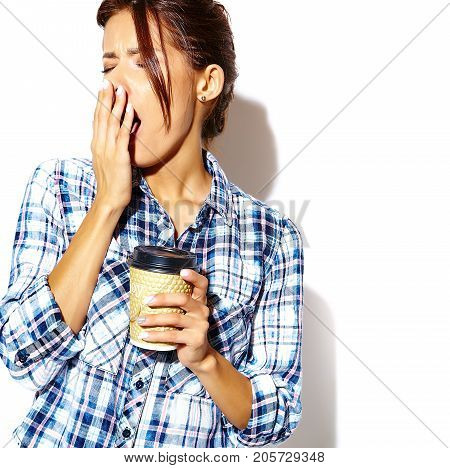 Portrait of beautiful stylish tired young woman drinking coffee in early morning yawning and holding plastic coffee cup on white background