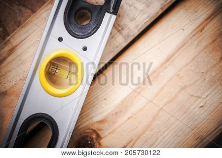 Spirit Level Tool or Bubble Level Instrument on Wooden Construction Materials Closeup Photo