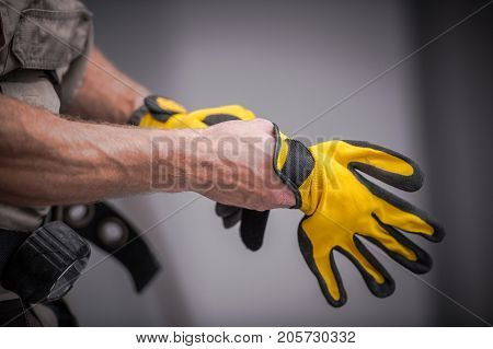 Wearing Construction Safety Gloves Closeup Photo. Caucasian Contractor Preparing For a Job.