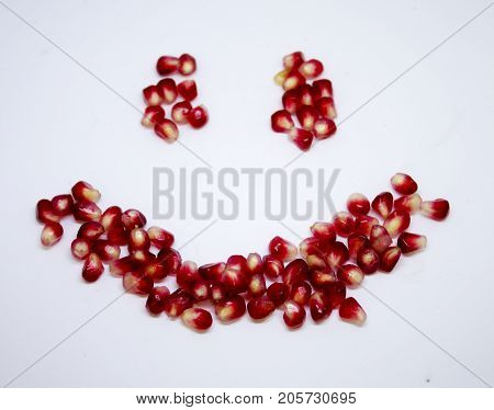 pomegranate seeds spilled on a white background