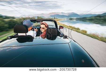 In love couple traveling by cabriolet car