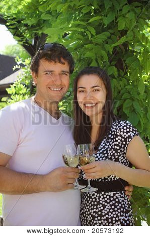 Couple Holding Glasses Of White Wine Making A Toast