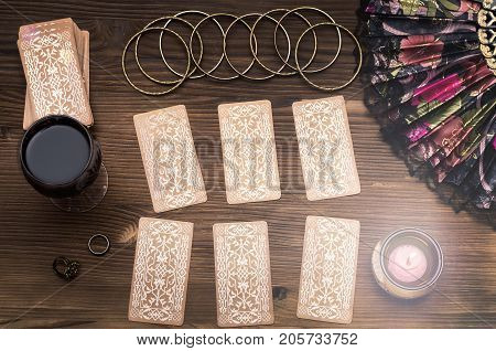Fortune teller female hands talismans and tarot cards on wooden table. Fortune teller concept. Divination.