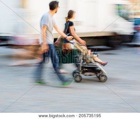 Young Family With Small Child In The  Stroller