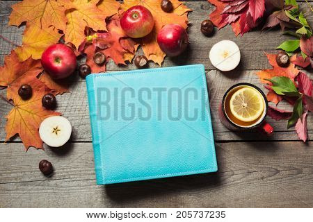 Fall concept. Blue album with space for text and cup of tea decor of autumn leaves apples on wooden board. Autumn still life. Top view.