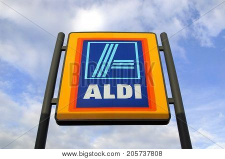 Swansea, UK: May 2016: Commercial sign of Aldi Store against a blue sky. Aldi is a large discount supermarket chain with approximately 4200 stores in Germany. It specializes in lower priced products.