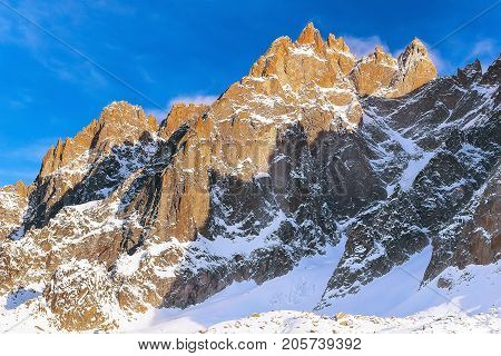 Winter snow mountains rocks in French Alps, Chamonix before sunset lightened with sun rays