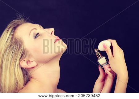 Smell elegance concept. Beautiful elegant blonde woman with necklace holding and applying perfume studio shot on dark background