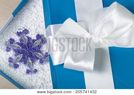 Opened Blue Box With White Bow On Its Top. Beautiful Paper Snowflake Surrounded By Styrofoam Balls I