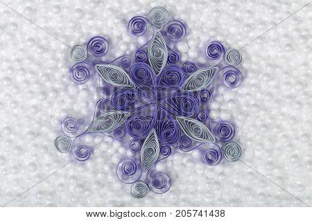Handmade Paper Snowflake On White Styrofoam Background.