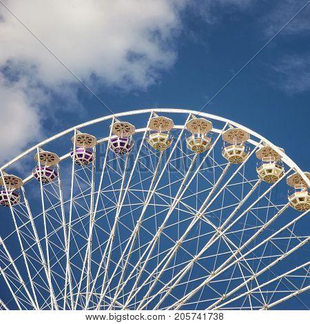 Carnival Ferris Wheel on blue sly with cloud backgroud