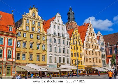 Wroclaw/Poland- August 17, 2017: cityscape of old town Market Square with colorful ornate historical buildings, outdoors restaurants with sunshades, citizens and tourists walking around
