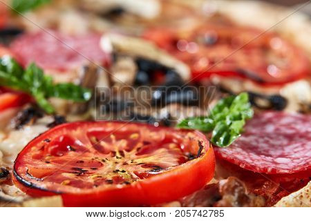 Closeup of pizza with salami, tomatoes, sausage, basil and olives