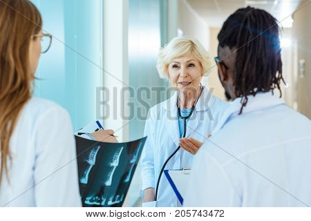 Senior doctor in lab coat telling something to young medical interns holding x-ray photograph