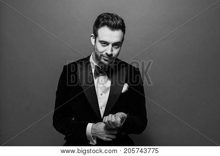 Black and white portrait of a businessman in a suit, white shirt and bow tie, putting on cufflinks and looking at the camera, against plain studio background.