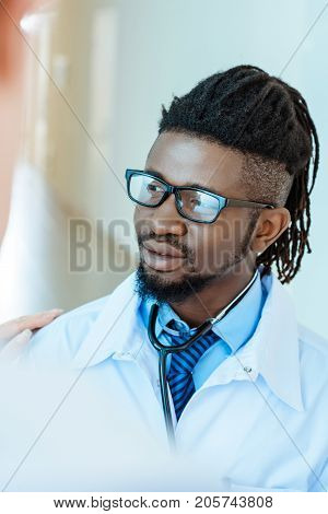 An african-american medical intern in lab coat and glasses