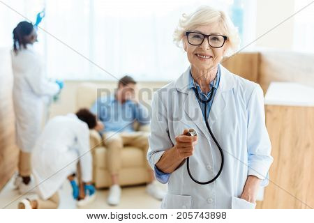 Senior doctor in lab coat and glasses smiling cheerfully and holding stethoscope in hospital enviroment