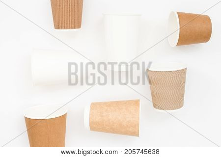 Craft and white disposable cups on white background. Top view geometry.