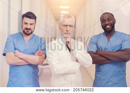 They are my interns. Delighted black man keeping smile on his face and crossing arms on chest while looking forward