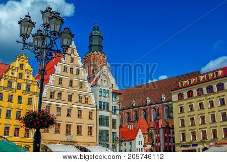 Wroclaw/Poland- August 17, 2017: cityscape of old town Market Square with colorful ornate historical buildings, street light, decorated with flowers, and part view of Saint Elisabeth Church over blue sky with clouds