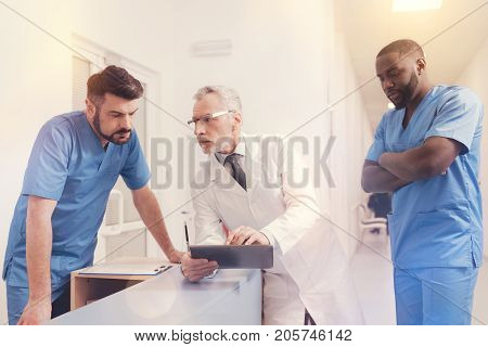 Show it to me. Serious elderly man wearing glasses and leaning on table while looking at his intern