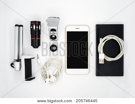 Flat lay (Top view) image of accessories (Tripod Phone Holder Universal Clamp Camera Lens Earphone Power Bank USB Charger Cable) around smartphone on white background